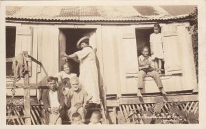 """""""Hawaiians at Home."""" You would never find an image of a multigenerational Hawaiian family living in a metal roofed shack in the tourist shops, but this shows real life. 1921"""