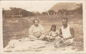 """This image of a Hawaiian family was actually sent by Nielen with this message: """"Fisher folks mending nets. If prayers were always answered, fishermen would not repair nets."""" 1923"""